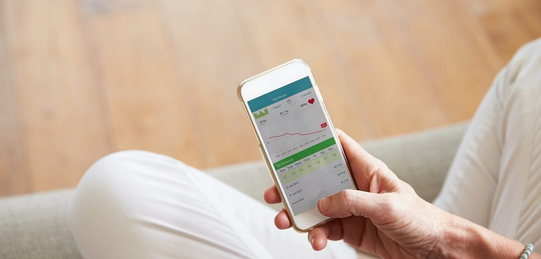 Woman Looking At Health Monitoring App On Smartphone