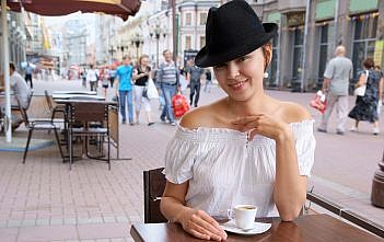 Young pretty woman in street cafe with cup